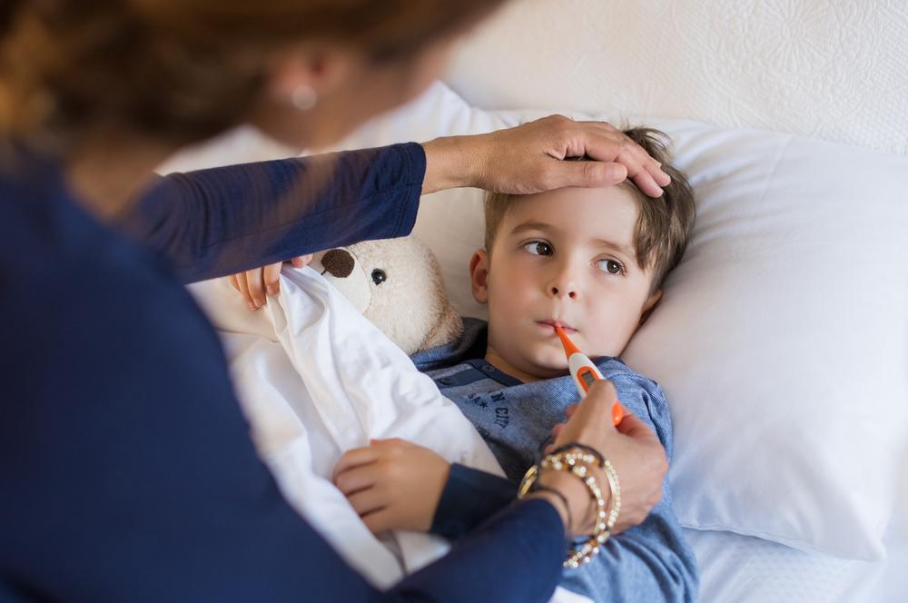 Mutter fühlt die Stirn eines kranken, im Bett liegenden Kindes und steckt ihm ein Fieberthermometer in den Mund